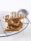 Heart-shaped waffles dusted with icing sugar on a wire rack