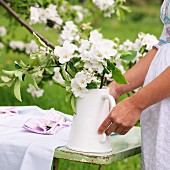 A woman carrying a jug of apple blossom