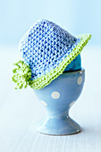 An Easter egg with a crocheted hat in an egg cup