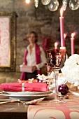 Gedeckter Weihnachtstisch in Pink, Frau mit Weihnachtsgeschenk