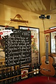 A menu on a blackboard next to a guitar in a Spanish bistro
