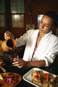 A Spanish woman pouring a glass of red wine