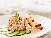 Smoked Trout Tartare with Sliced Cucumbers and Grilled Italian Bread Slices on a White Plate