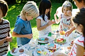 Children selecting sweets from table at outdoor birthday party