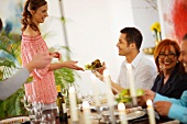 Gedeckter Tisch; Frau reicht Salatteller