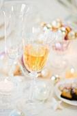 Gedeckter Weihnachtstisch mit Wein, Sektglas und Gebäck