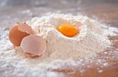 An egg yolk and an eggshell in flour on a wooden slab