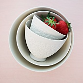 Two strawberries in white, overturned ceramic bowls