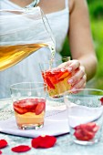A woman pouring cold spiced wine into glasses of strawberries