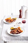 Fried beef steak with fried onions, arranged on two plates