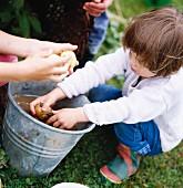 A girl washing potato in a garden.