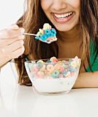 Frau isst Cerealien mit Milch