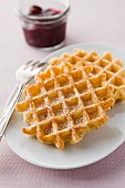 Waffles with icing sugar and cherry jam