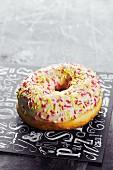 Ein Doughnut mit Zuckerglasur und -perlen