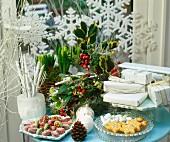 Weihnachtstisch mit Blumendeko, Geschenken, Kerzen und Weihnachtsplätzchen vor Fenster mit dekorativen Schneeflocken