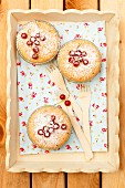 Mini cakes with redcurrants and icing sugar on a wooden tray