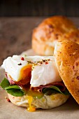 A spinach, bacon and poached egg sandwich (close-up)