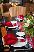 Festlich gedeckter Weihnachtstisch mit weihnachtlichem Gesteck in der Tischmitte; im Hintergrund das Feuer im offenen Kamin