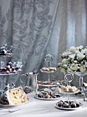 Weihnachtstisch mit gezuckerten Trauben, Panettone, Pralinen und weissen Rosen