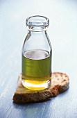 Olive oil in small bottle and a slice of bread