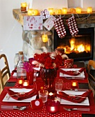 Rot gedeckter Weihnachtstisch vor einem Kamin