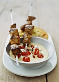 Meat kebabs with garlic sauce and cherry tomatoes