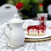 White coffee pot and piece of cake on table in open air