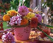 Dahlien, Chinaschilf und Hagebutten in pinkfarbener Vase