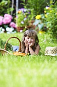 A little girl laying in a garden next to a basket of carrots