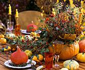 Herbstliches Blumengesteck und Zierkürbisse auf dem Tisch
