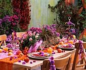 Gedeckter Tisch mit Blütengirlanden und Äpfeln