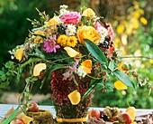 Herbststrauss im Topf mit Callunablüten umwickelt
