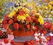 Gesteck aus Herbstchrysanthemen und Lampionblumen