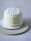 Small white cake decorated with icing