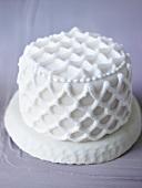 Small white cake with lattice decoration