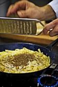 Grating truffle over ribbon pasta