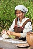 Girl in Viking costume kneading bread dough