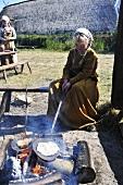 Girl in Viking costume baking flatbread on campfire
