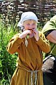 Blond girl in Viking costume eating carrot