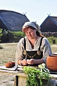 Woman in Viking costume preparing vegetables
