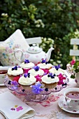 Cupcakes with violets on cake stand, tea