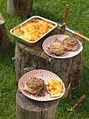 Bacon-wrapped entrecote steak and loin of pork with potato gratin