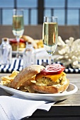 A fish burger and a glass of champagne on a table overlooking the sea