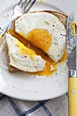 A plate of fried egg on toast with cutlery