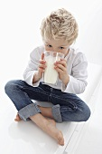 A little boy drinking a glass of milk