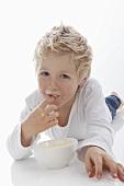 A little boy tasting a bowl of milk