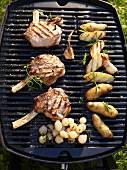 Barbecued veal chops, potatoes and pearl onions on barbecue