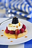 Sweet pizza topped with raspberries, cream and caramel sauce