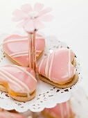 Heart-shaped biscuits with pink icing on tiered stand