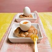 Geöffnetes Frühstücksei mit einem selbstgebackenen Eierbecher
